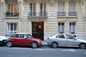 Cars parked along a Parisian sidewalk.